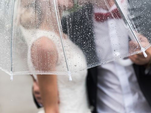the bride and groom in the rain are covered with a transparent umbrella rain drops